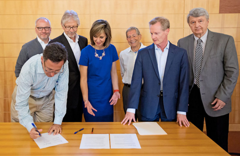 people standing around table, signing document.